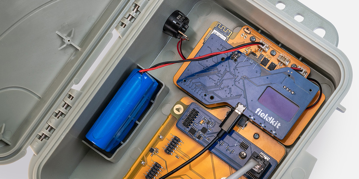 Closeup image of interior of FeildKit enclosure, showing micro USB plugged in and battery pack in addition to the boards